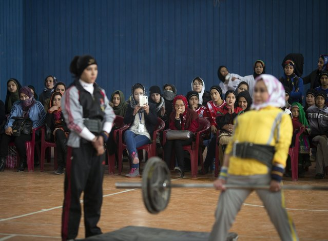 An Afghan female power-lifter demonstrates during a local sport ceremony in a stadium in Kabul March 8, 2014. (Photo by Morteza Nikoubazl/Reuters)
