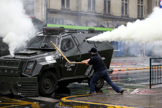 A demonstrator hits a riot police vehicle during a rally commemorating May Day in Santiago, Chile May 1, 2016. (Photo by Ivan Alvarado/Reuters)
