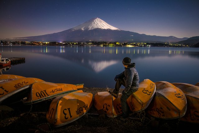 """""""Moonlit Scene at Mt. Fuji"""". The moon was so bright and the scene was illuminated by the moonlight. The water was so still make the heritage mountain of Japan mt. fuji reflect in the water of lake kawaguchiko makes this landscape a sense of a place. Photo location: Lake Kawaguchiko, Yamanashi, Japan. (Photo and caption by Danilo Dungo/National Geographic Photo Contest)"""