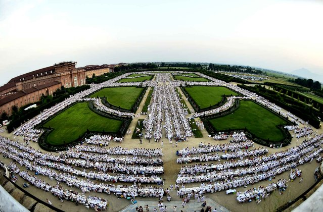 "More than 14,000 people dressed in white sit in the Venaria Reale Garden during a flash mob-style ""Cena in Bianco"" (""Dinner in White""), in Venaria Reale near Turin on July 05, 2015. The ""Diner en Blanc"" is a chic secret pop-up style picnic phenomenon originally started in France. (Photo by Giuseppe Cacace/AFP Photo)"