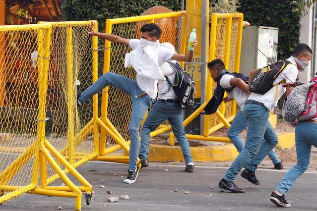 A student kicks a fence during a protest to demand the government to repeal a law that requires high school seniors to teach at least two people to read and write, as part of a graduation programme in Tegucigalpa, Honduras, May 4, 2016. (Photo by Jorge Cabrera/Reuters)