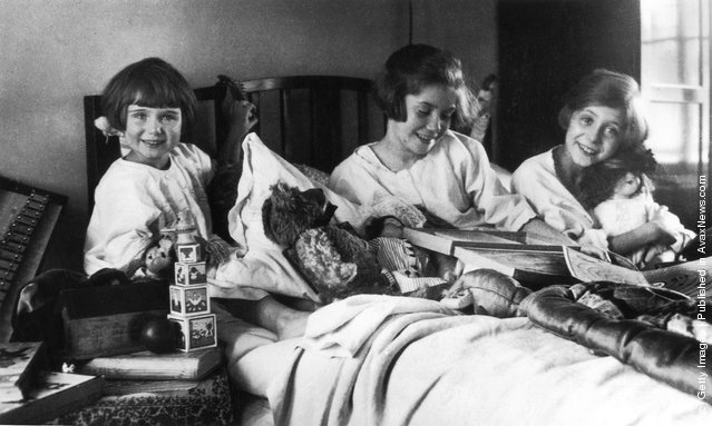 1925: Three girls on Christmas morning delighted with their gifts from Father Christmas