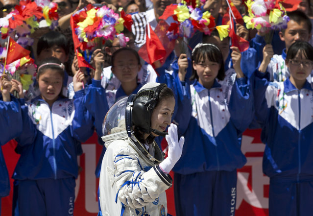 Chinese students wave flowers and national flags as female astronaut Wang Yaping leaves the Jiuquan satellite launch center for the launch site, near Jiuquan in western China's Gansu province, Tuesday, June 11, 2013. (Photo by Andy Wong/AP Photo)