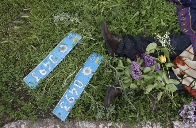 Two number plates are seen next to the body of a Ukrainian policeman outside the police headquarters after an Ukrainian forces attempt to drive out pro-Russian militants in Mariupol May 9, 2014. Ukrainian security forces killed about 20 pro-Russian rebels who tried to seize control of police headquarters in the eastern port city of Mariupol on Friday, the Interior Minister said. (Photo by Marko Djurica/Reuters)