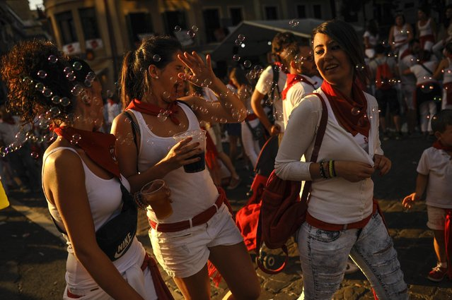 A group of revelers shaking soap bubbles as they enjoy the day  at the San Fermin Festival, in Pamplona, Spain, Saturday, July 11, 2015. Revelers from around the world arrive to Pamplona every year to take part during the eight days of the running of the bulls. (Photo by Alvaro Barrientos/AP Photo)
