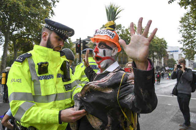 A climate activist is detained by police as others gather at Parliament Street in London, Monday, October 7, 2019. London Police say they've arrested 21 climate change activists over the past few days as the Extinction Rebellion group attempts to draw attention to global warming. (Photo by Alberto Pezzali/AP Photo)