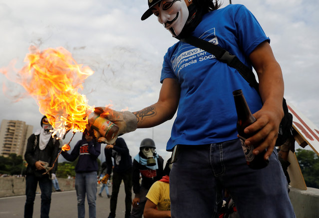 A demonstrator prepares to throw a molotov cocktail during clashes with riot police while rallying against Venezuela's President Nicolas Maduro in Caracas, Venezuela on May 2, 2017. (Photo by Carlos Garcia Rawlins/Reuters)