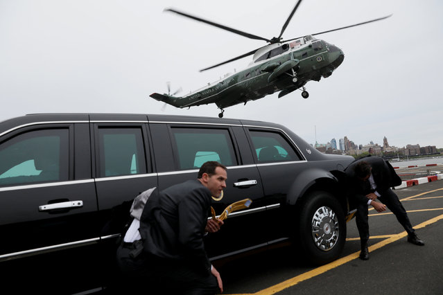 Secret Service agents use a presidential limousine for cover from spraying water as U.S. President Donald Trump lands via Marine One helicopter in New York, U.S. May 4, 2017. (Photo by Jonathan Ernst/Reuters)