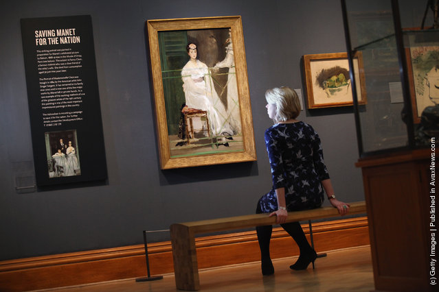 A woman sits near a painting by Edouard Manet entitled 'Portrait of Mademoiselle Claus' from 1868 in the Ashmolean Museum