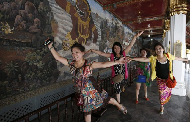 Chinese tourists pose for a picture inside the Grand Palace in Bangkok May 24, 2014. The Thai army's imposition of martial law is another blow to the country's tourist industry, adding to the economic pain from six months of destabilizing street protests as airlines cut back on flights and concern over insurance adds to travelers' worries. (Photo by Erik De Castro/Reuters)