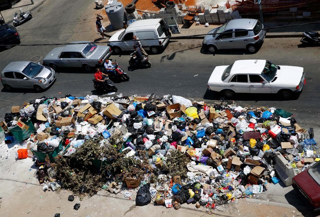 Cars and motorcycles pass by a large pile of garbage on a Beirut street, Lebanon, Tuesday, July 21, 2015. Garbage piled up on the streets of Beirut amid a growing dispute over Lebanon's largest trash dump. (Photo by Hassan Ammar/AP Photo)