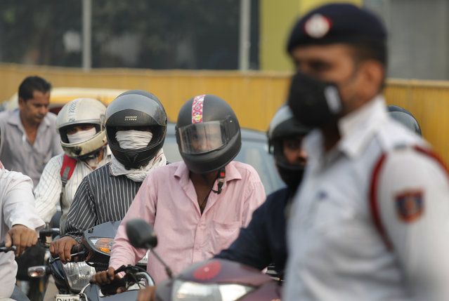 Motorcyclists cover their faces with scarf to save themselves from air pollution as they wait at a crossing in New Delhi, India, Monday, November 4, 2019. (Photo by Manish Swarup/AP Photo)