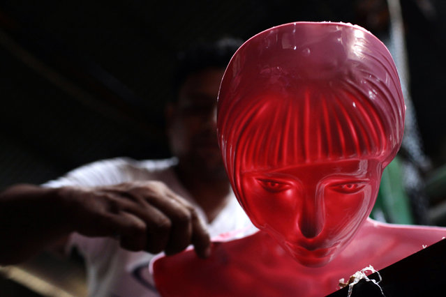 A Bangladeshi man works at a factory that manufactures plastic mannequins in Dhaka, Bangladesh, on May 30, 2014. Workers at the factory earn less than US$5 a day. (AP Photo/A.M. Ahad)