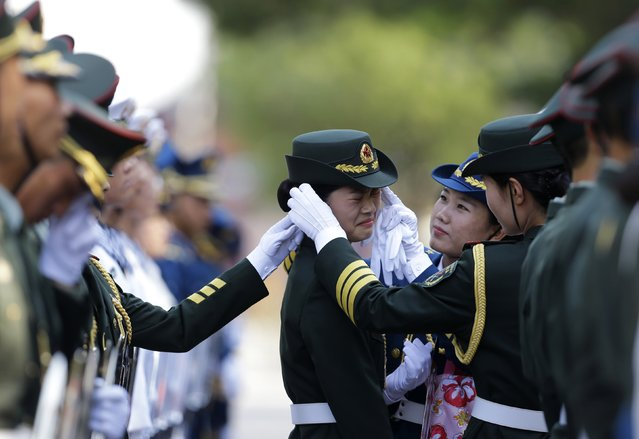 A female member of the honour guard reacts as another one helps to adjust her cap ahead of an official welcoming ceremony for Italy's Prime Minister Matteo Renzi outside the Great Hall of the People in Beijing, June 11, 2014. (Photo by Jason Lee/Reuters)