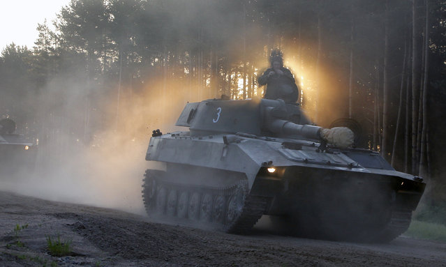 A soldier surrounded by smoke and dust sits on top of a Belarus army self-propelled artillery tank as they head to the rehearse for the Independence Day military parade in outskirts of Minsk, Belarus, early Tuesday, May 31, 2016. The parade will take place on July 3. (Photo by Sergei Grits/AP Photo)