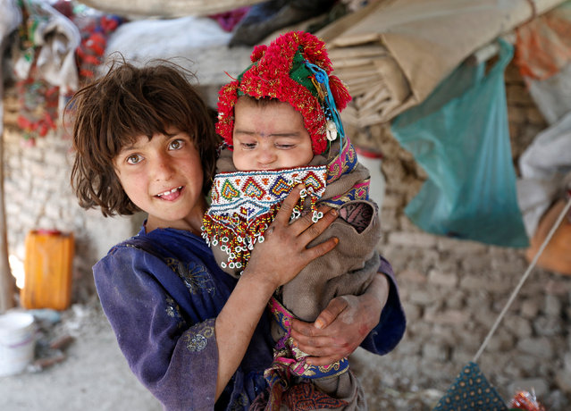 An internally displaced Afghan girl holds a child at a refugee camp in Kabul, Afghanistan May 31, 2016. (Photo by Mohammad Ismail/Reuters)