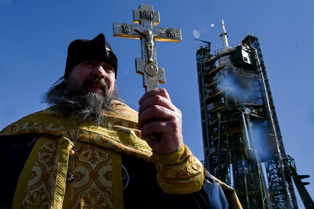 A Russian Orthodox priest conducts a blessing in front of the Soyuz TMA-20M spacecraft at the launch pad of the Russian-leased Baikonur cosmodrome on March 17, 2016. (Photo by Kirill Kudryavtsev/AFP Photo)