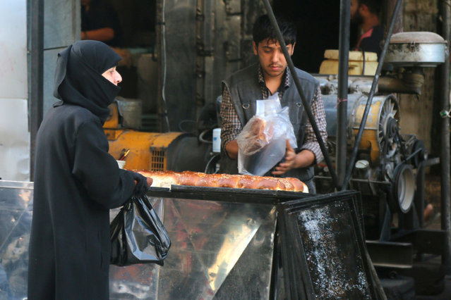 A vendor sells traditional sweets on the first day of the holy fasting month of Ramadan in the rebel held al-Shaar neighborhood of Aleppo, Syria, June 6, 2016. (Photo by Abdalrhman Ismail/Reuters)