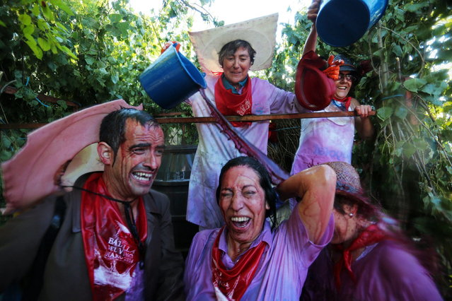 """A reveler pours wine on people as they take part in the """"Battle of Wine"""" (La batalla del vino de Haro), a wine fight, during the Haro Wine Festival, in Haro, in the northern province of La Rioja on June 29, 2014. More than nine thousand locals and tourists threw around 130.000 litres of wine at each other during the Haro Wine Festival, according to local media. (Photo by Cesar Manso/AFP Photo)"""