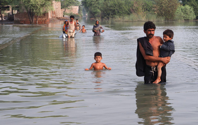 Pakistani villagers wade through floodwaters in Layyah, Pakistan, Saturday, July 25, 2015. (Photo by Asim Tanveer/AP Photo)