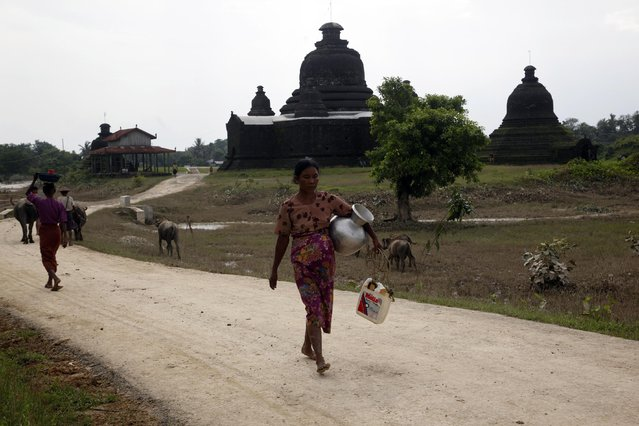 A woman carrying a container walks to fetch water at a well near a pagoda in Myauk U, Rakhine State, western Myanmar, Tuesday, August 4, 2015. (Photo by Khin Maung Win/AP Photo)