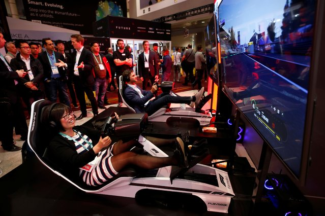 How Hong (L) of Canada tries out a driving simulator in the Formula One Esports League booth during the 2020 CES in Las Vegas, Nevada, U.S. January 7, 2020. (Photo by Steve Marcus/Reuters)