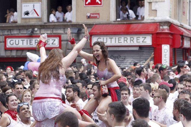 """Revellers celebrate moments before the rocket fire or """"Txupinazo"""" marks the start of the Festival of San Fermin (or Sanfermines) at Consistorio square in Pamplona, Spain, 06 July 2014. (Photo by Javier Lizin/EFE)"""