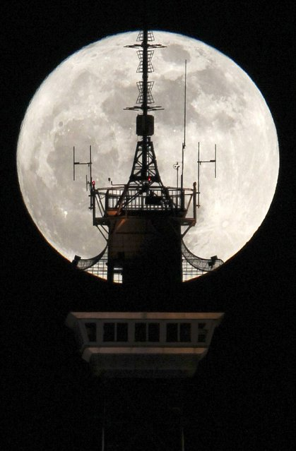 """The moon is seen behind the top of the radio and television tower """"Funkturm"""" in Berlin March 19, 2011. Saturday will see the rise of a full moon called a """"Super Moon"""" when it arrives at its closest point to the Earth in 2011, a distance of 221,565 miles or 356,575 km away"""