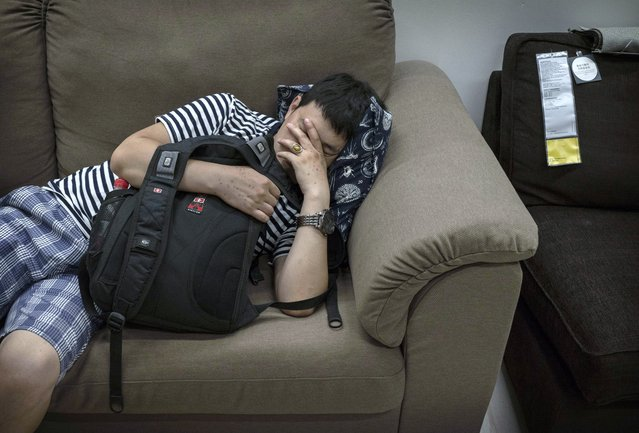 A Chinese shopper sleeps on a sofa in the showroom of the IKEA store on July 6, 2014 in Beijing, China. Of the world's ten biggest Ikea stores, 8 of them are in China to cater to the country's growing middle class. The stores are designed with extra room displays given the tendency for customers to make a visit an all-day affair. Store management does not discourage shoppers from sleeping on Ikea furniture, even marking them with signs inviting customers to try them out. (Photo by Kevin Frayer/Getty Images)