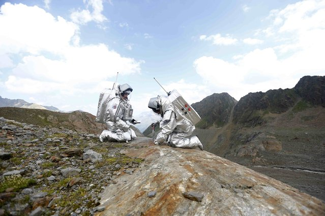 Inigo Munoz Elorza of Spain and Stefan Dobrovolny of Austria (R) take stone samples during a simulated Mars mission on Tyrolean glaciers in Kaunertal, Austria, August 7, 2015. (Photo by Dominic Ebenbichler/Reuters)