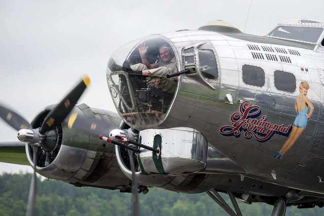 "Roger Hadfield, father of Canadian astronaut Chris Hadfield, waves from the bombardier's seat after ""Sentimental Journey"", a Second World War B-17 Flying Fortress, lands at Gatineau Executive Airport in Gatineau, Quebec, on Monday, July 7, 2014. The Royal Canadian Air Force flew the B-17 out of RCAF Station Rockcliffe in Ottawa, delivering mail to Canadian soldiers, sailors and airmen overseas. Hadfield flew the B-17 in the 1960s to conduct aerial mapping. (Photo by Justin Tang/AP Photo/The Canadian Press)"