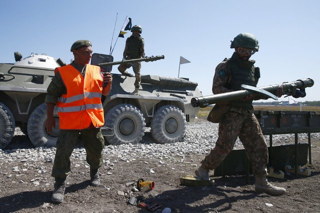 A serviceman from Pakistan (R) carries a Russian-made Igla ground-to-air launcher next to a referee after firing during the Air defense battle masters competition as part of the International Army Games 2015 in the port town of Yeysk, Russia, August 9, 2015. (Photo by Maxim Zmeyev/Reuters)