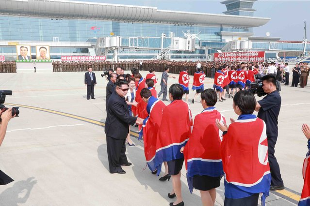 North Korean leader Kim Jong Un and his wife Ri Sol Ju greet North Korea's female soccer team as they arrive at Pyongyang International Airport on Monday after winning the 2015 EAFF East Asian Cup, in this undated photo released by North Korea's Korean Central News Agency (KCNA) in Pyongyang on August 10, 2015. (Photo by Reuters/KCNA)