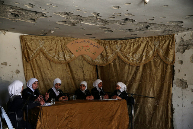 """Girls attend a discussion under a riddled roof during a celebration marking the end of the school year in the town of Douma, eastern Ghouta in Damascus, Syria May 21, 2016. The sign on the curtain reads in Arabic, """"Childhood in the United Nations, between the dream and reality"""". (Photo by Bassam Khabieh/Reuters)"""
