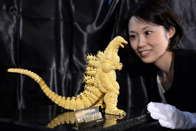 A Ginza Tanaka employee looks at 24-cm-tall and 15-kilogram gold statue of Godzilla unveiled during a press preview of the Godzilla exhibition in Tokyo on July 19, 2014. The Godzilla statue will take orders starting on July 20 at the Ginza Tanaka jewelry shop with a price of 150 million yen (about 1.48 million USD). (Photo by Toshifumi Kitamura/AFP Photo)