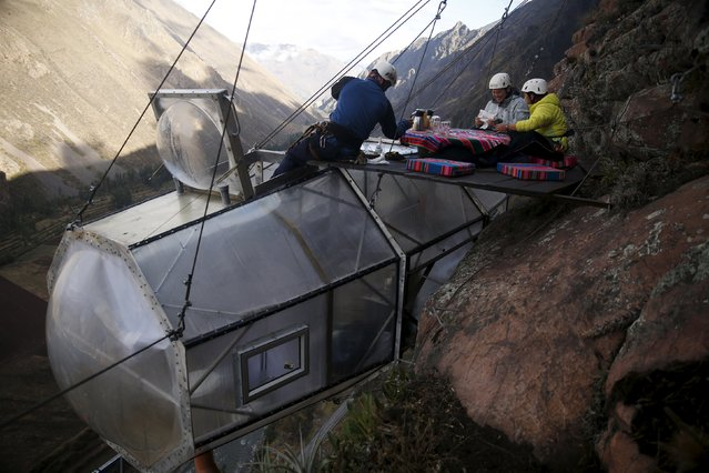 A guide (L) serves breakfast to guests above the cabine at the Skylodge Adventure Suites in the Sacred Valley in Cuzco, Peru, August 14, 2015. (Photo by Pilar Olivares/Reuters)