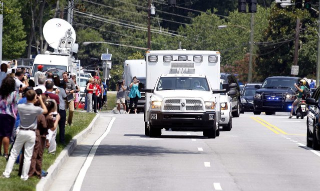 An ambulance carrying American missionary Nancy Writebol, 59, who is infected with Ebola in West Africa arrives past crowds of people taking pictures at Emory University Hospital in Atlanta, Georgia August 5, 2014. Writebol arrived in the United States after being flown overnight from Liberia and will be treated by infectious disease specialists at Emory University Hospital, according to Christian missionary group SIM USA.(Photo by Tami Chappell/Reuters)