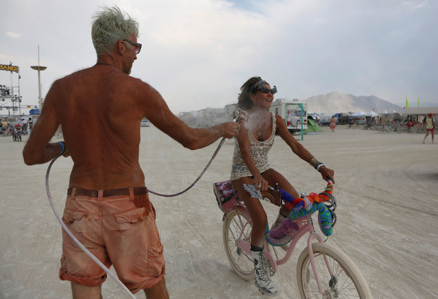 Participants get misted by compressed air and water as approximately 70,000 people from all over the world gathered for the annual Burning Man arts and music festival in the Black Rock Desert of Nevada, U.S. on  on August 31, 2017. (Photo by Jim Urquhart/Reuters)