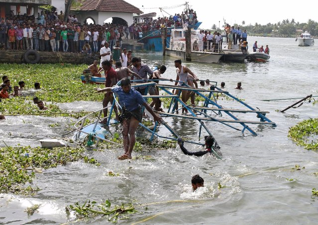 A rescue team member jumps from the damaged ferry as it is pulled to the banks after it capsized in the waters of Vembanad Lake at Fort Kochi in the southern state of Kerala, India, August 26, 2015. (Photo by Sivaram V/Reuters)