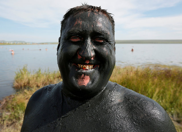A man covered with mineral-rich mud smiles on a bank of lake Tus in Khakassia region, southwest of the Siberian city of Krasnoyarsk, Russia, July 16, 2016. (Photo by Ilya Naymushin/Reuters)
