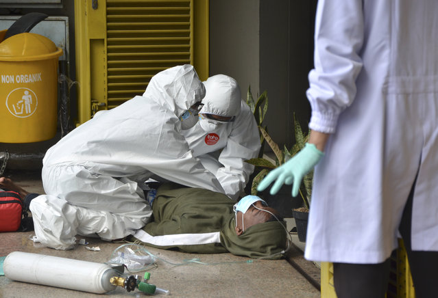 Paramedics wearing protective suits amid fears of coronavirus outbreak check on a man who collapsed outside a clinic in Jakarta, Indonesia, Thursday, March 26, 2020. It's not immediately clear what caused the man to collapse. The U.S. Embassy in Indonesia has ordered the departure of employees' family members under the age of 21 from its missions in the country where new COVID-19 patients have surged in the past week with high fatality. (Photo by Muchlis Akbar/AP Photo)
