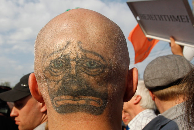 """A protester with a face tattooed on the back of his head takes part in the """"march of the million"""" opposition protest in central Moscow, on May 6, 2012. Russian riot police beat protesters with batons and hauled away dozens on Sunday after skirmishes broke out at a demonstration in Moscow against Vladimir Putin on the eve of his return to the presidency. (Photo by Denis Sinyakov/Reuters)"""