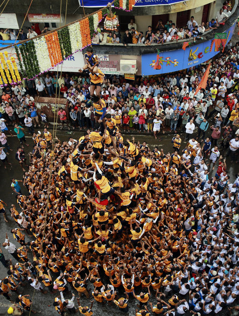 """Indian youth form a human pyramid to break the """"Dahi handi"""", an earthen pot filled with curd, an integral part of celebrations to mark Janmashtami in Mumbai, India, Monday, August 18, 2014. (Photo by Rafiq Maqbool/AP Photo)"""