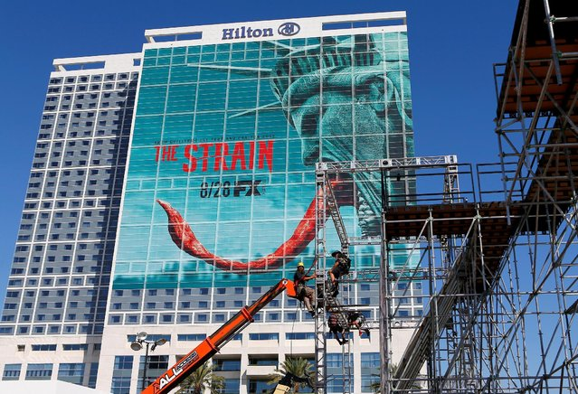 Workers put up scaffolding next to a hotel covered with an advertising sign as attendees gather for the start of Comic-Con International in San Diego, California, United States, July 20, 2016. (Photo by Mike Blake/Reuters)