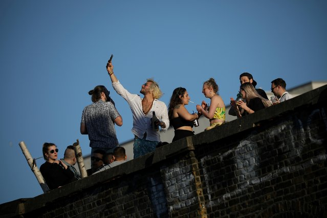 People enjoy warm weather on a rooftop as the spread of the coronavirus disease (COVID-19) continues, in London, Britain, April 5, 2020. (Photo by Marika Kochiashvili/Reuters)