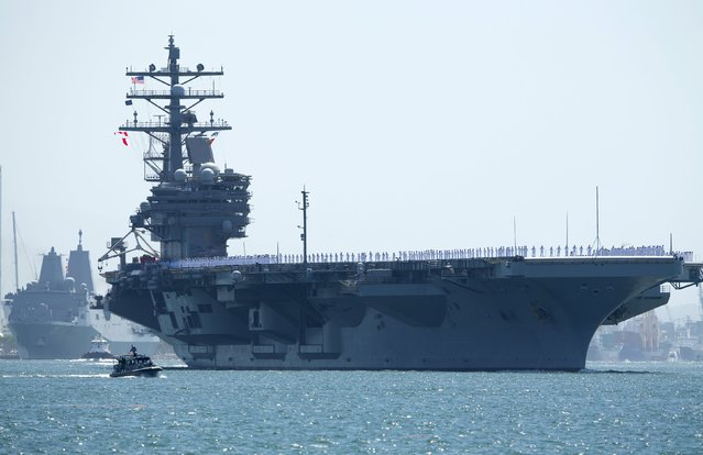 The USS Ronald Reagan, a Nimitz-class nuclear-powered super carrier, is followed by the USS Somerset as it departs for Yokosuka, Japan from Naval Station North Island in San Diego, California  August 31, 2015. The Reagan is replacing the USS George Washington as part of a complicated three-carrier swap that exchanges crews for ships, saving the Navy millions in moving costs. (Photo by Mike Blake/Reuters)