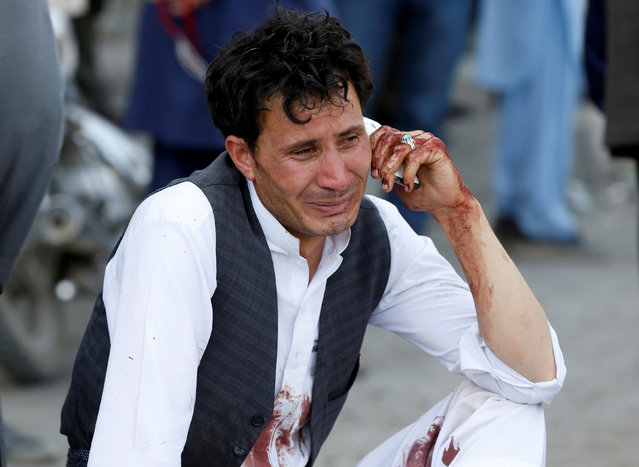 A bloodied man who carried dead and wounded, speaks on the phone at the site of a suicide attack an explosion that struck a protest march, in Kabul, Afghanistan, Saturday, July 23, 2016. Witnesses in Kabul say that an explosion causing multiple casualties struck the march by members of Afghanistan's largely Shiite Hazara ethnic minority group, who were demanding that a major regional electric power line be routed through their impoverished home province. (Photo by Omar Sobhani/Reuters)