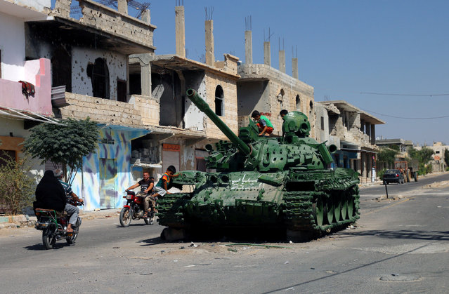 People ride on their motorbike near a damaged military tank that belonged to forces loyal to Syria's President Bashar al-Assad in the rebel-held southern town of Bosra al-Sham, Deraa Governorate, Syria September 19, 2017. (Photo by Alaa Al-Faqir/Reuters)