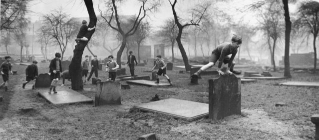 A group of boys from the Gorbals play amongst the gravestones of the Corporation Burial Ground in Rutherglen Road, UK, one of the few areas of greenery in the district, 1948. (Photo by Bert Hardy)
