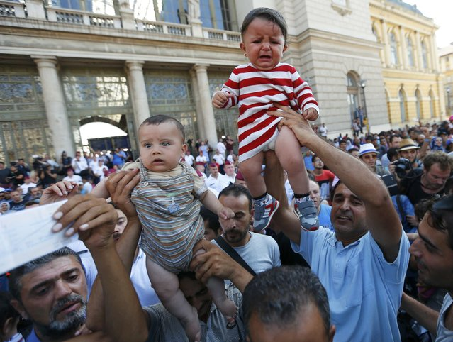 Migrants wave their train tickets and lift up children outside the main Eastern Railway station in Budapest, Hungary, September 1, 2015. (Photo by Laszlo Balogh/Reuters)